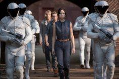 Katniss Everdeen (Jennifer Lawrence, vorne), Peeta Mellark (Josh Hutsherson, Mitte), Haymitch Abernathy (Woody Harrelson, hinten) flankiert von Friedenswächtern